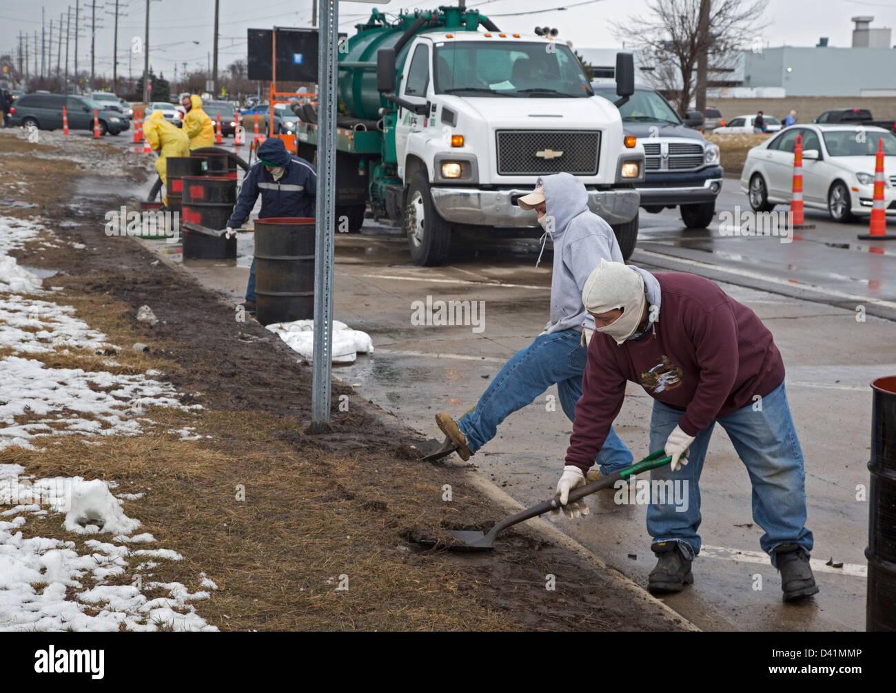 Warren, Michigan - Trabajadores limpiar un derrame de materiales peligrosos en el hombro de una calle principal. Imagen De Stock