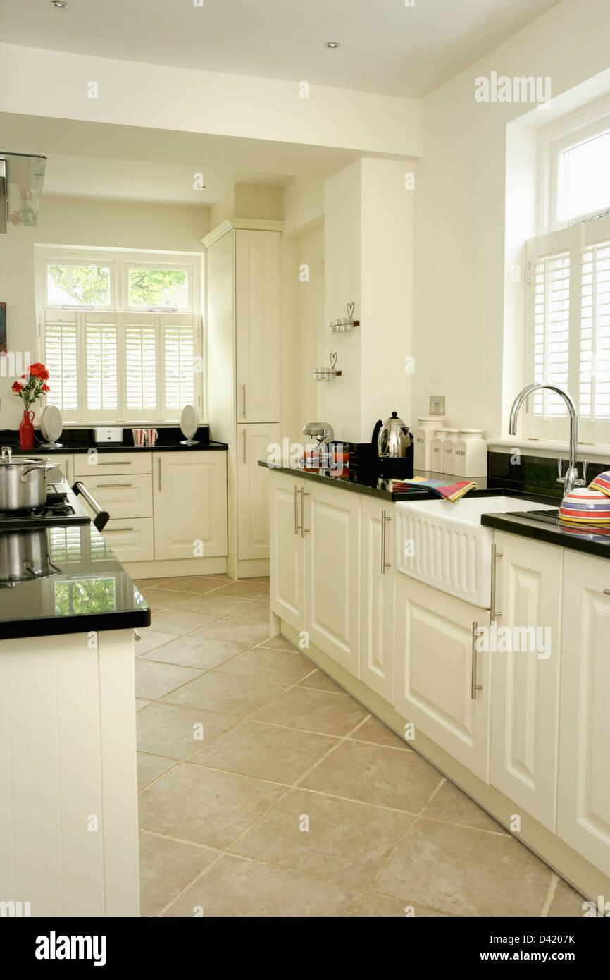Suelo de baldosas de piedra caliza blanca en la moderna cocina con encimeras de granito negro sobre blanco provisto de unidades