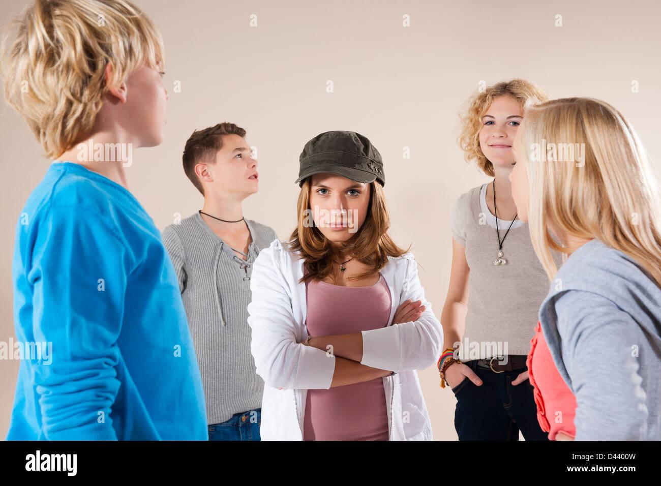 Retrato de una adolescente vistiendo Baseball Hat mirando a la cámara, de pie en medio del grupo de adolescentes Foto de stock