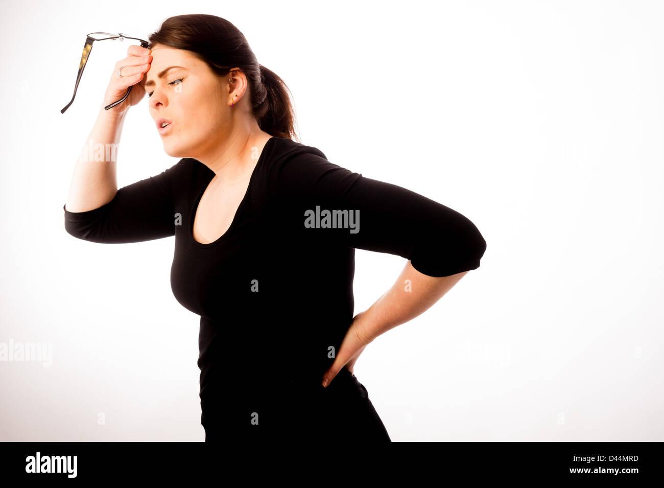 Una mujer joven, de cabello castaño, sufriendo de dolor de espalda, el estrés la tensión UK, Imagen De Stock