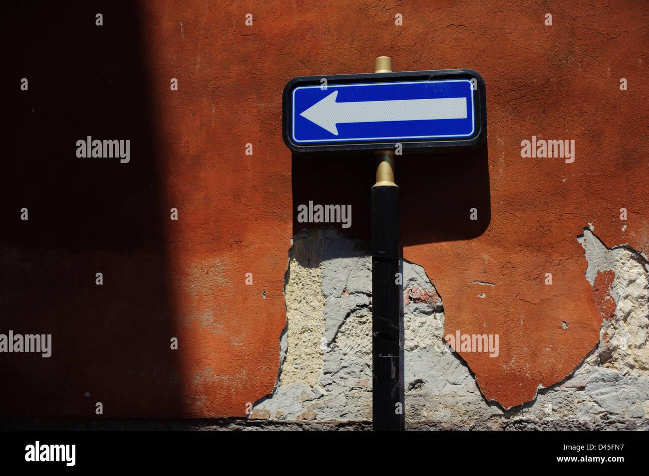 Signo de flecha azul y blanca contra una pared naranja, Verona, Italia. Imagen De Stock