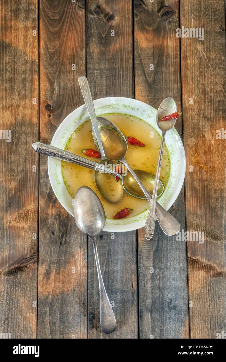 Plato de sopa con los chiles picantes y cinco cucharas Imagen De Stock