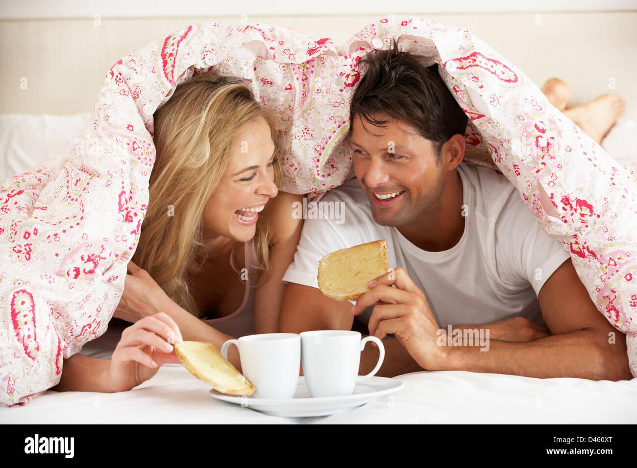 Pareja acurrucada bajo el edredón desayunando Foto de stock