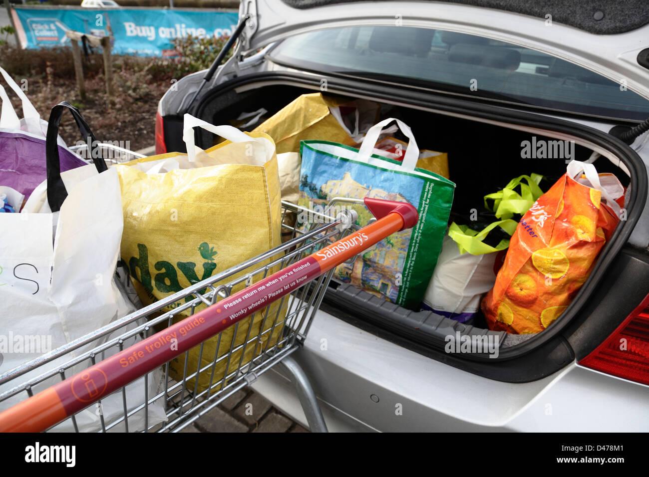 Bolsas de la compra en un carrito del supermercado Sainsbury's y el maletero del coche, Scotland, Reino Unido Imagen De Stock