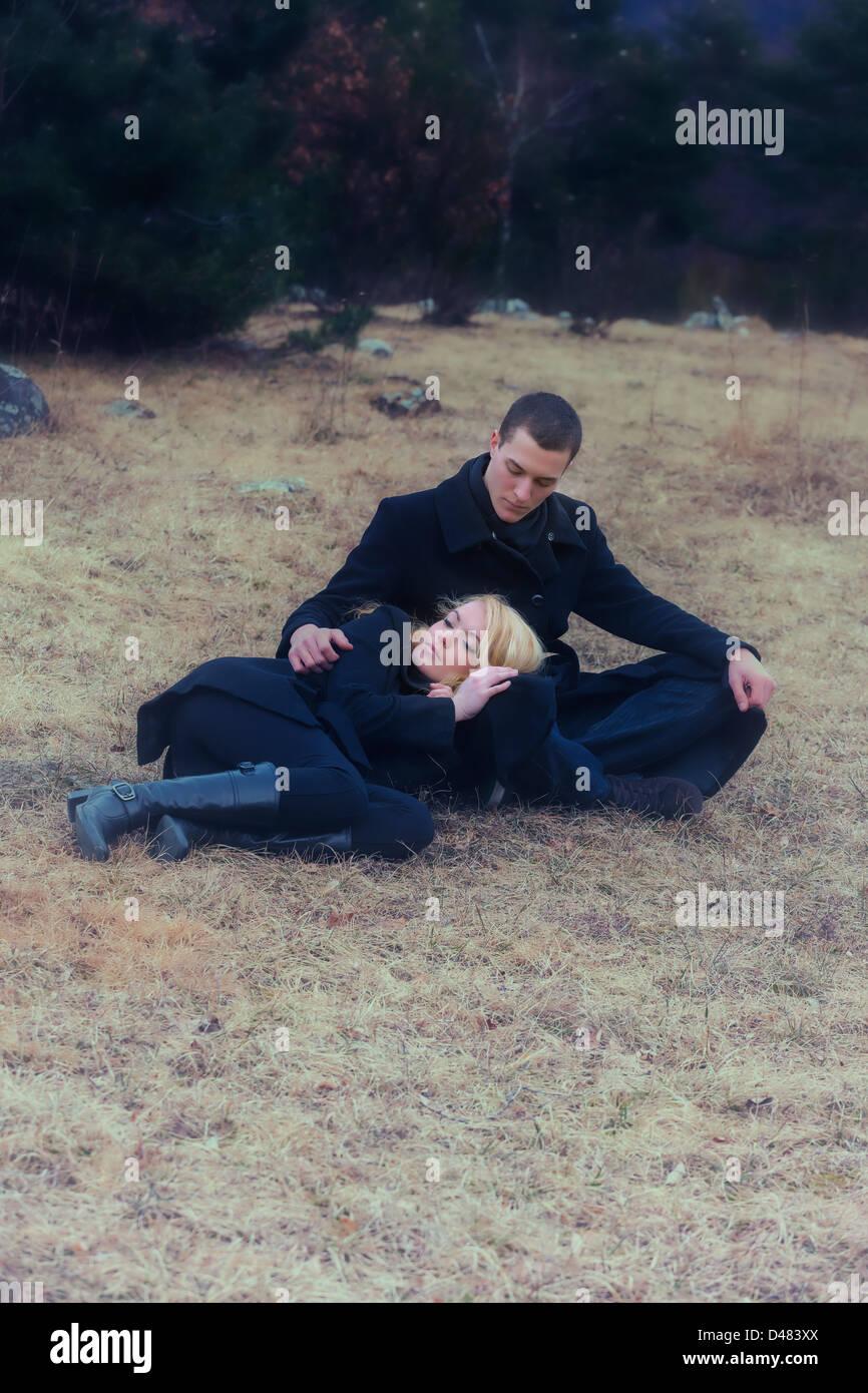 Una pareja en ropa negra está tumbado sobre una pradera en invierno Imagen De Stock