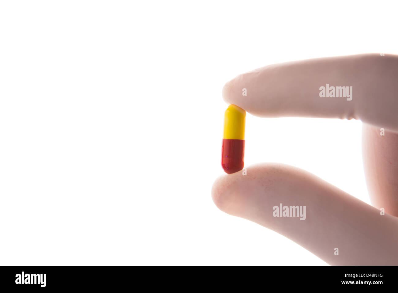 Mano enguantada sosteniendo cápsula tablet Foto de stock