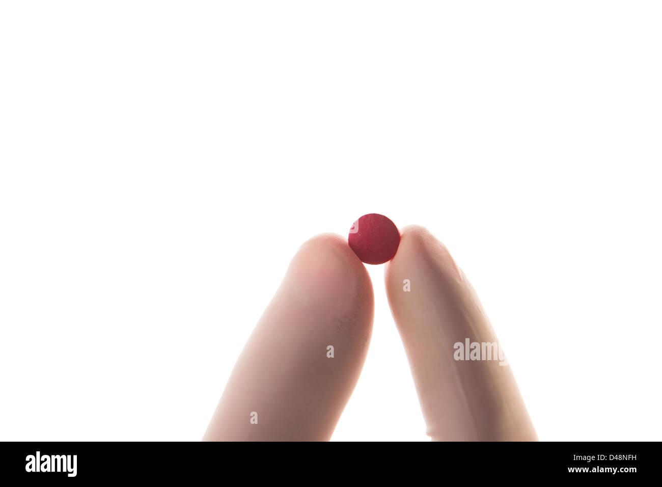 Mano enguantada sosteniendo pastilla roja Foto de stock