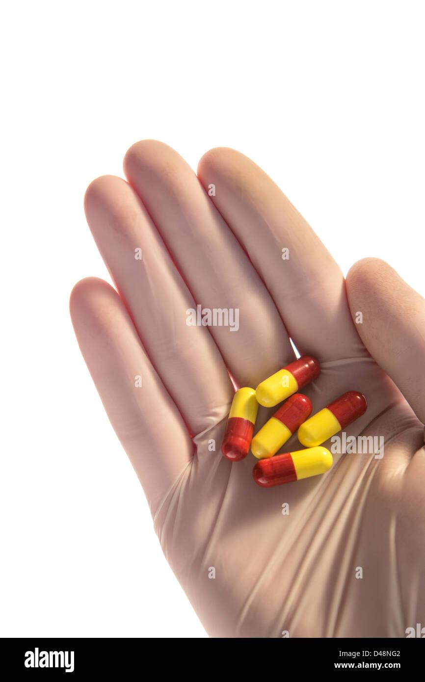 Mano enguantada sosteniendo los comprimidos en palm Foto de stock