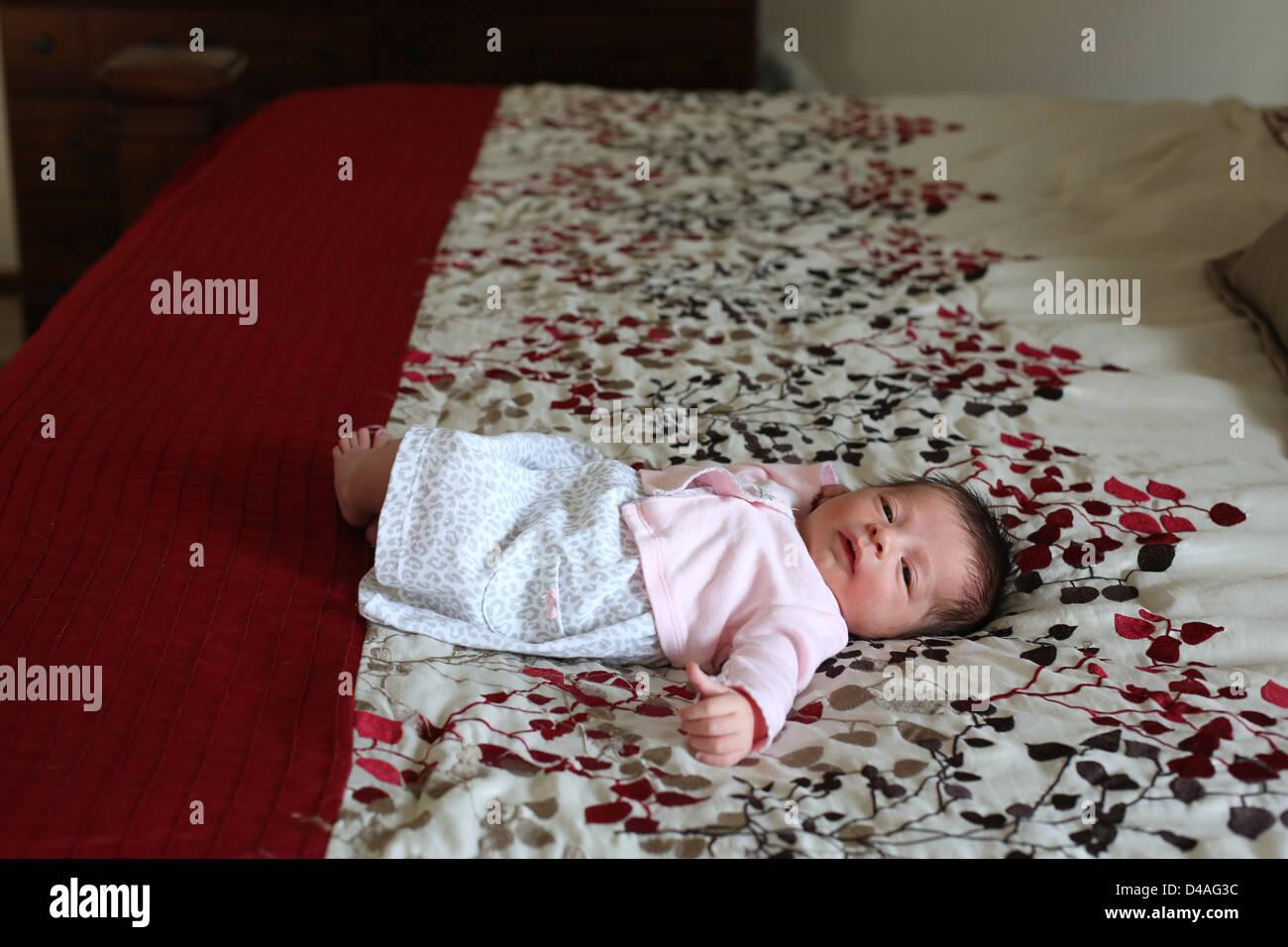 Un pequeño bebé recién nacido acostado en una cama grande. Foto de stock
