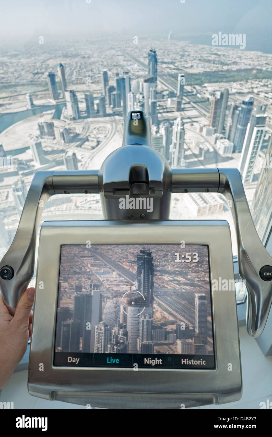 Telescopio de video y pantalla para observar Dubai desde la plataforma de observación en la cima de la torre Burj Foto de stock