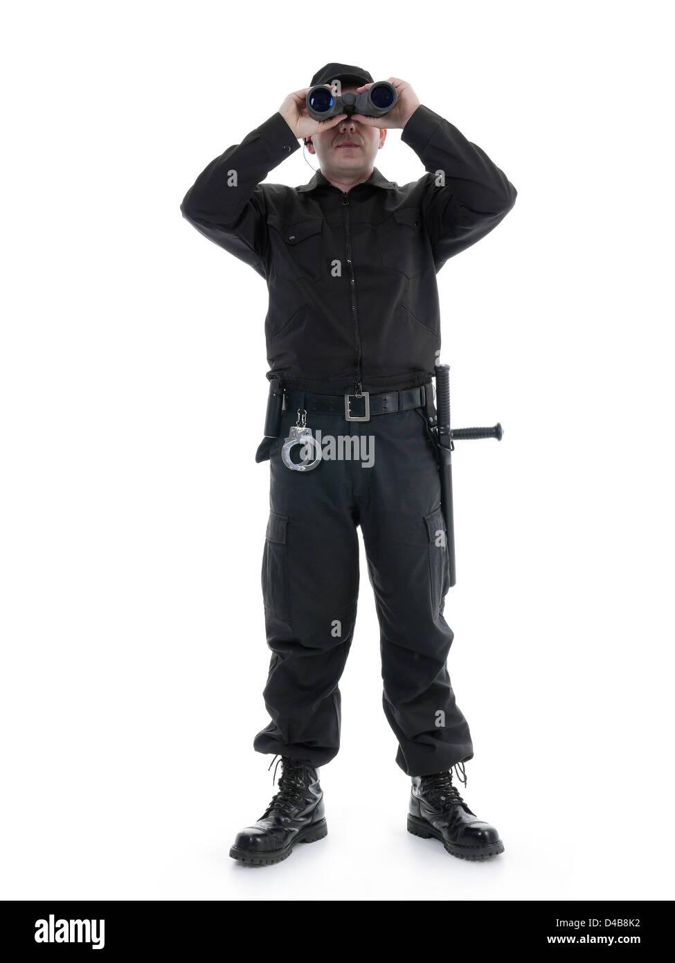 Hombre de seguridad vistiendo uniforme negro mirando a través de binoculares, rodada en blanco Imagen De Stock
