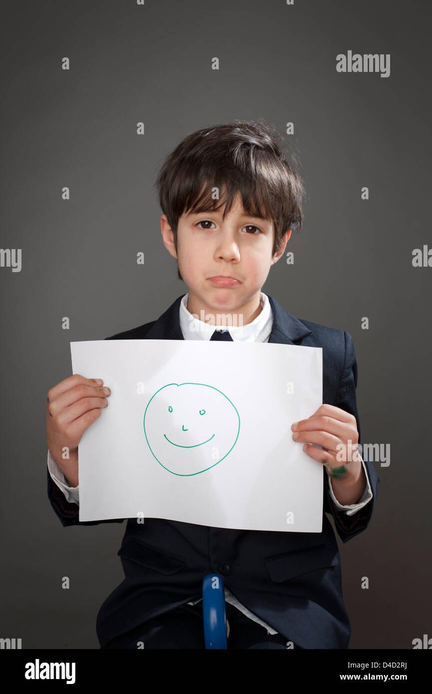 Triste muchacho con dibujo de cara feliz Imagen De Stock