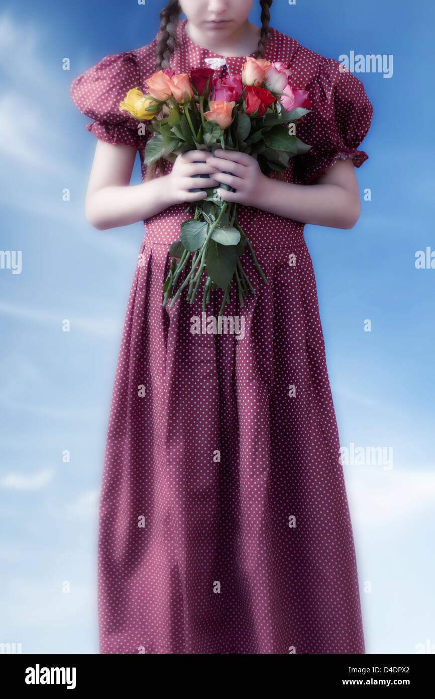 Una niña en un vestido rojo sosteniendo un ramo de flores Imagen De Stock