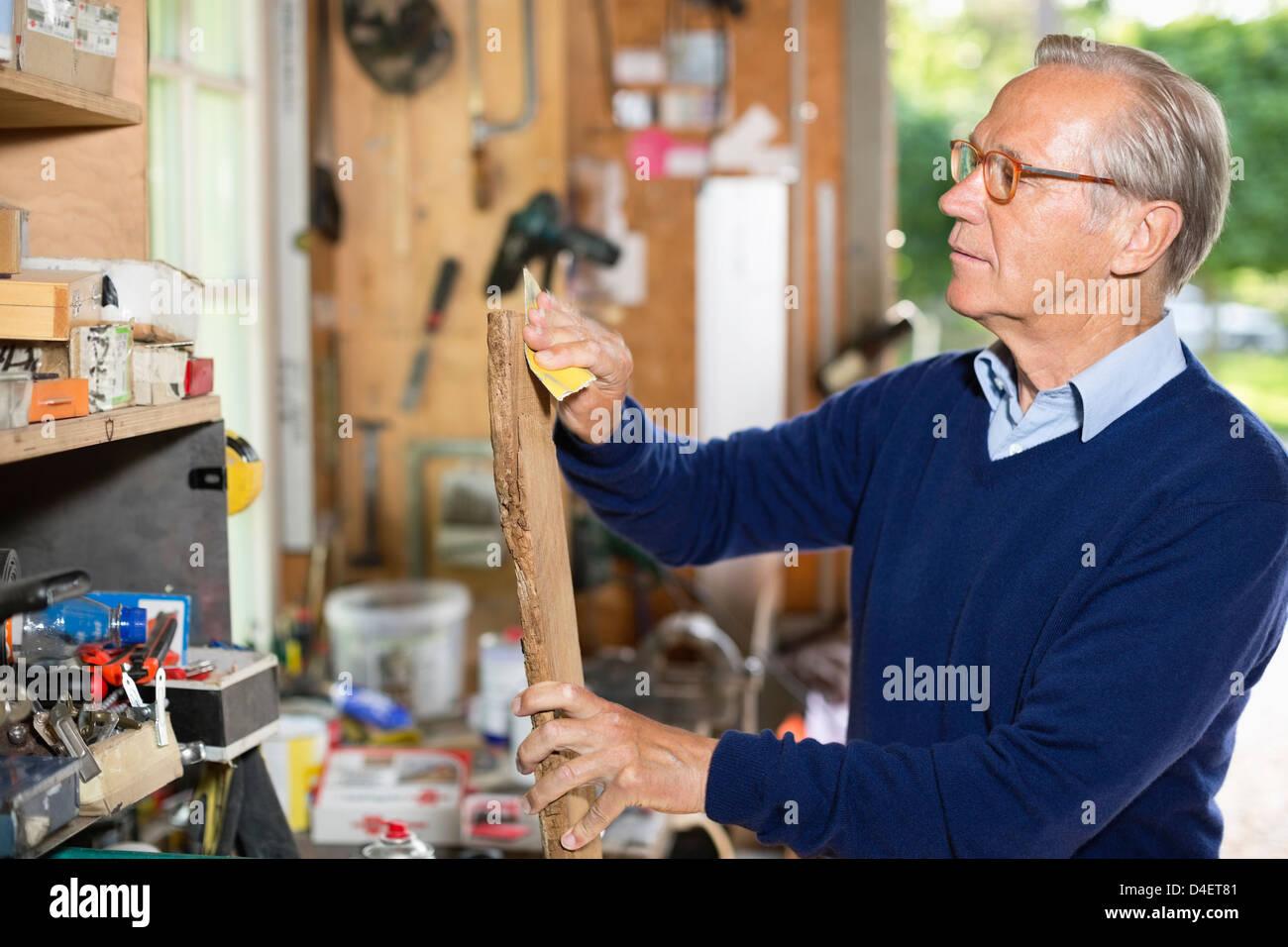 El hombre lija madera en garaje Imagen De Stock