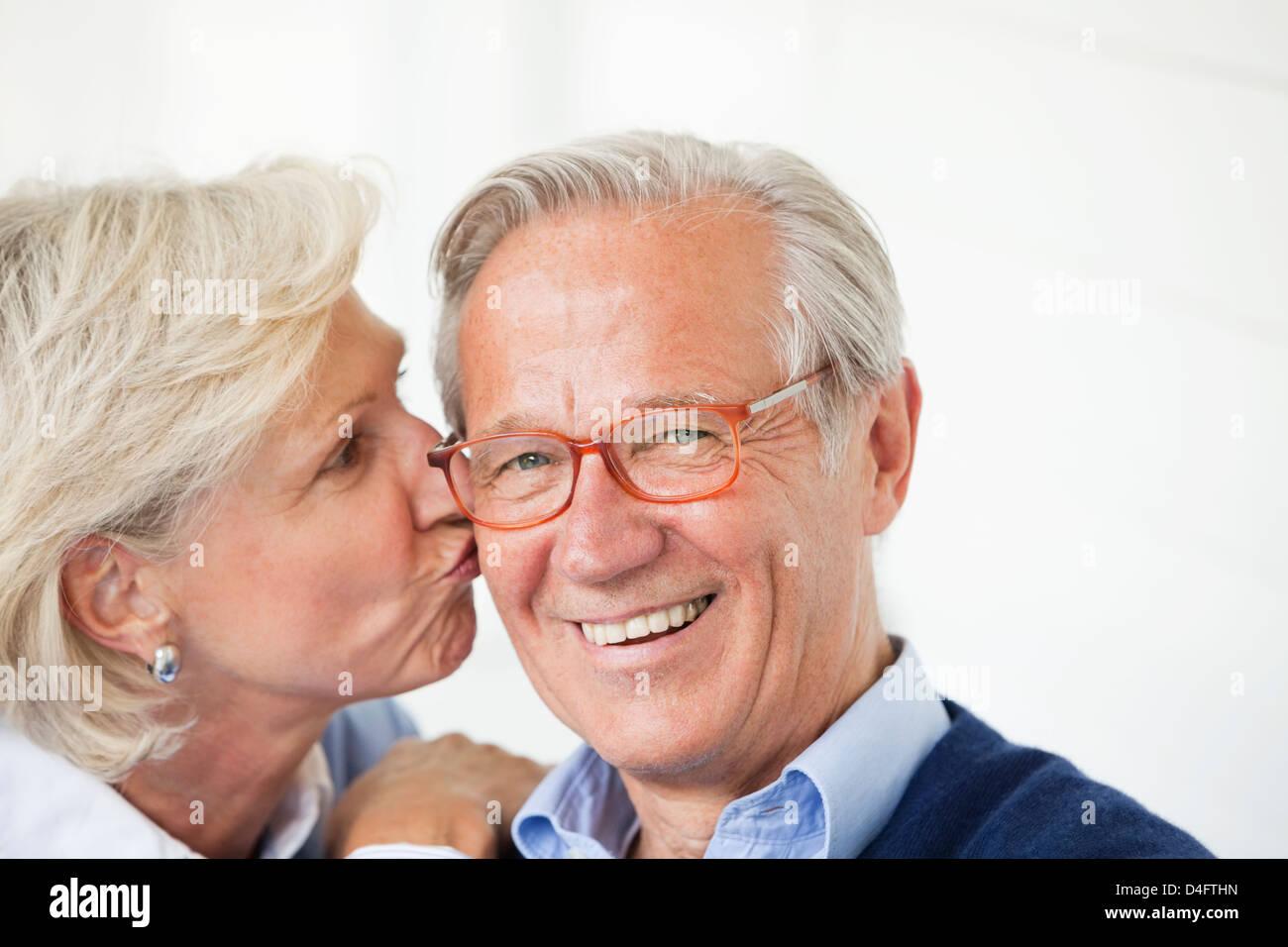 Mujer sonriente besando marido Imagen De Stock