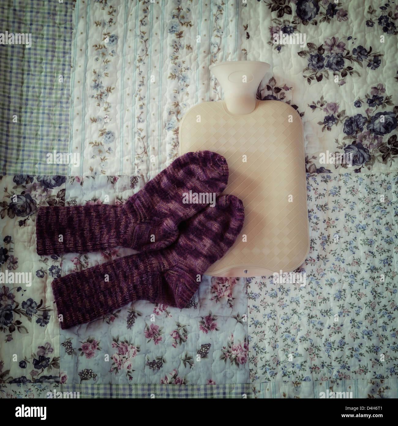 Botella de agua caliente con calcetines tejidos a mano en una cama vintage Foto de stock