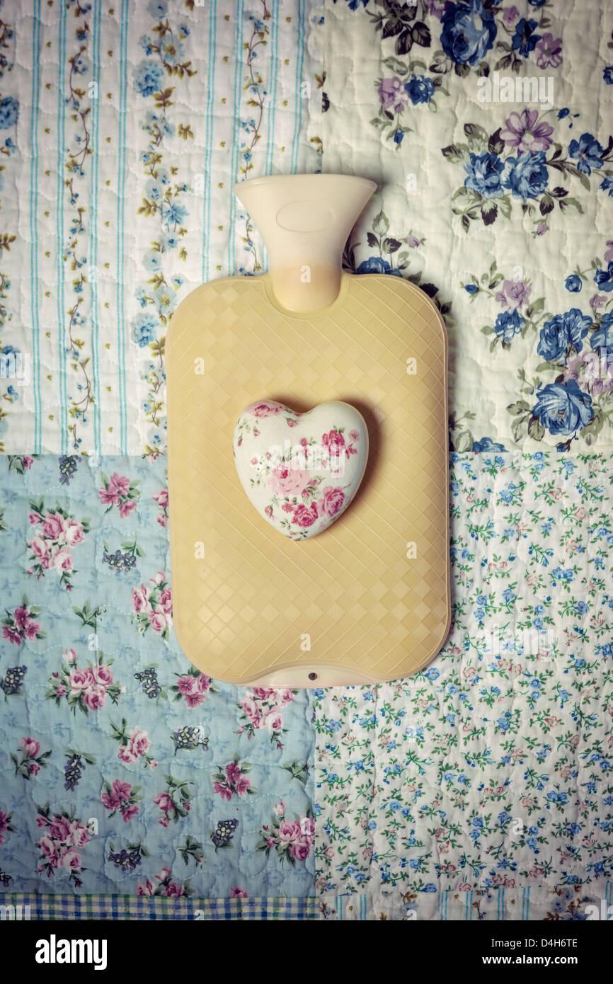 Una botella de agua caliente en una cama vintage con un corazón floralFoto de stock