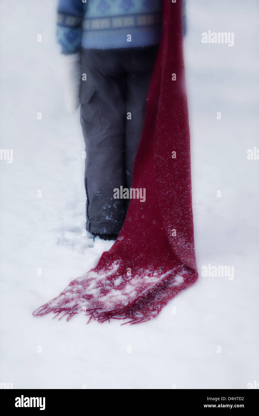 Una chica con un pañuelo rojo en la nieve. Imagen De Stock