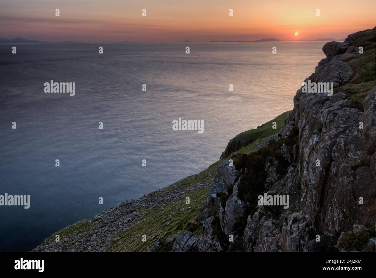 Puesta de sol sobre las Hébridas Exteriores de Neist Point, Isla de Skye, Escocia Foto de stock
