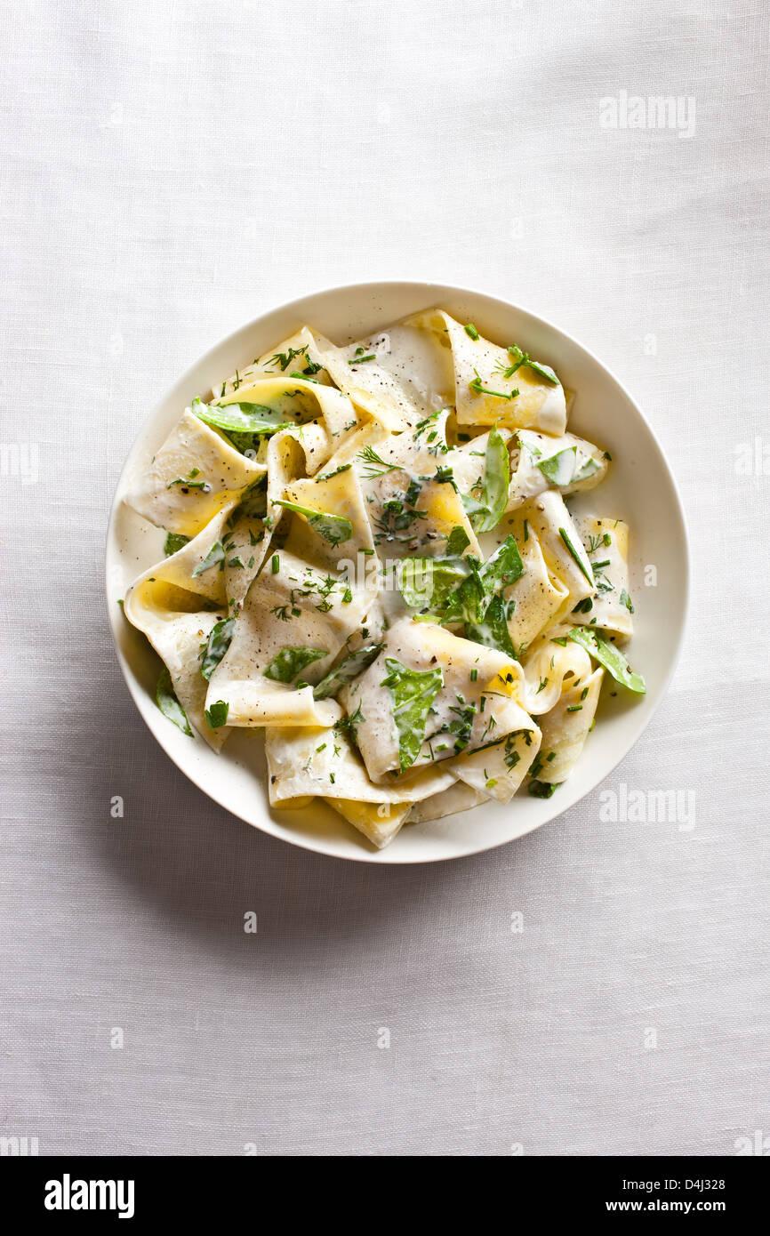 Un plato de pasta pappardelle con crema de requesón, baby de espinacas frescas, hierbas y pimienta negra. Imagen De Stock