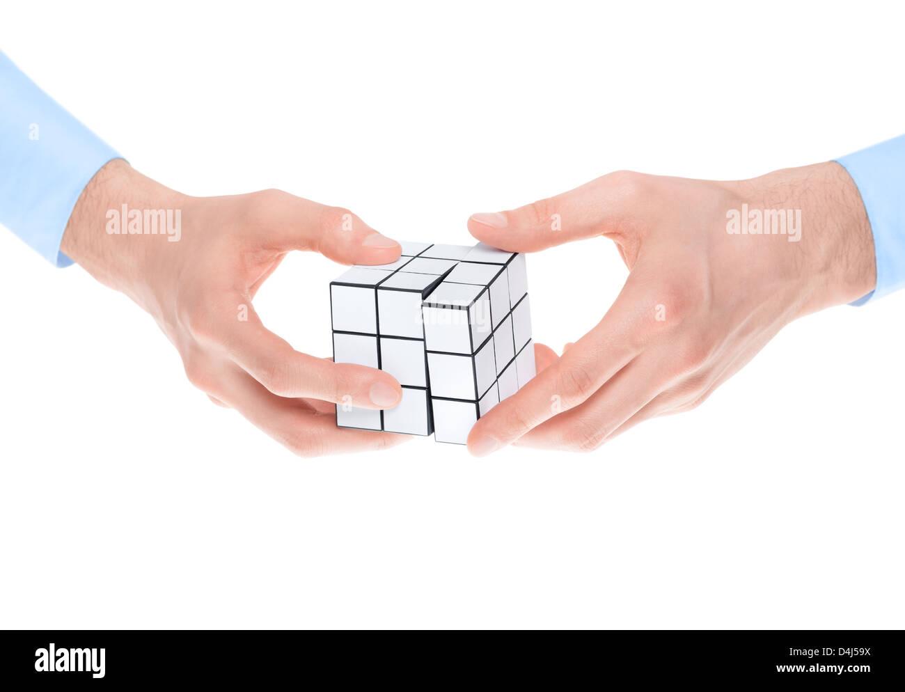 Las manos masculinas en shirtsleeves resolver un puzzle twist en blanco. Aislado en blanco. Imagen De Stock