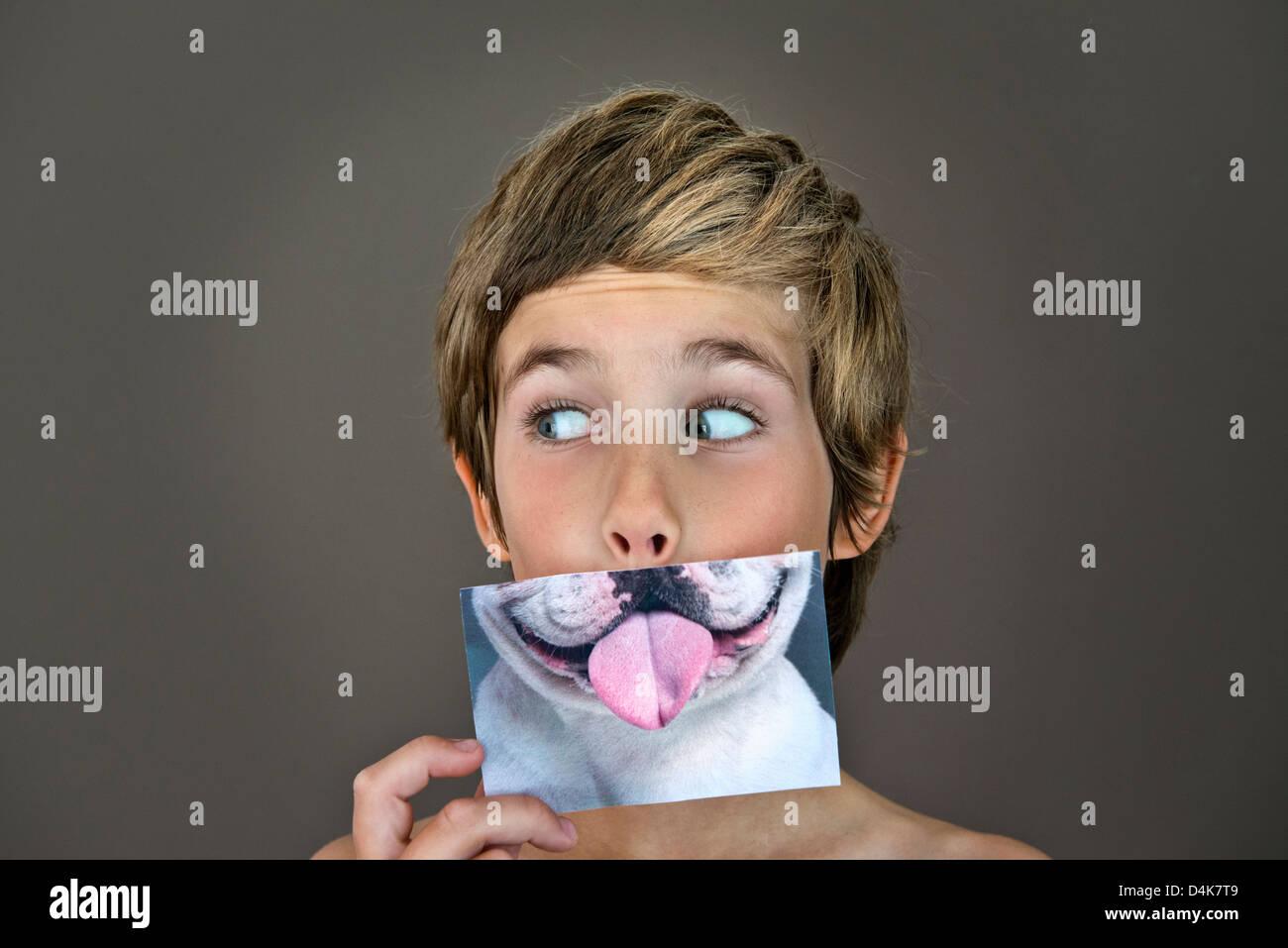 Niño sosteniendo la imagen sobre la cara de perro Imagen De Stock
