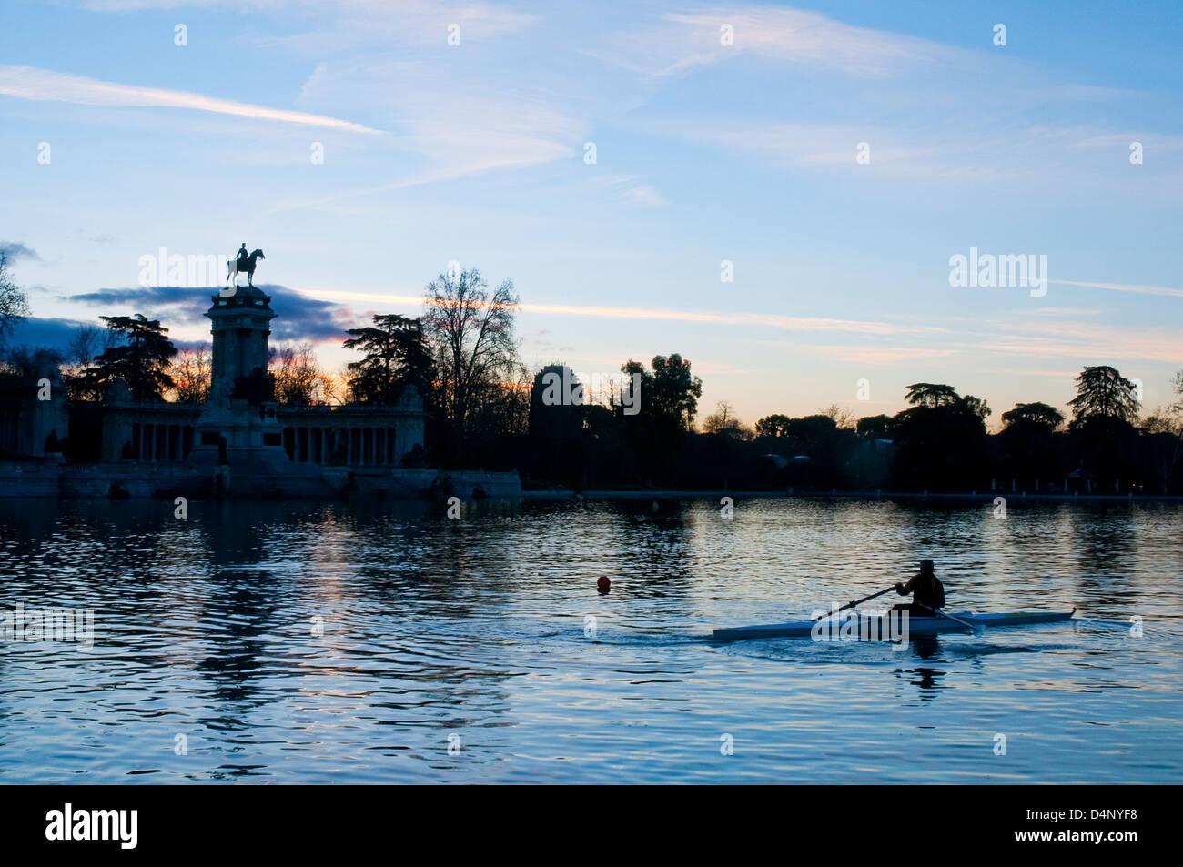 Hombre de remar en el amanecer en el estanque. El parque del Retiro, Madrid, España. Foto de stock