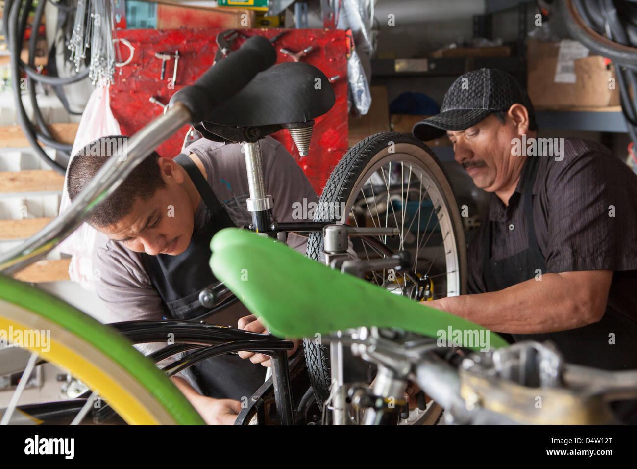 Mecánica trabajando en la tienda de bicicletas Imagen De Stock
