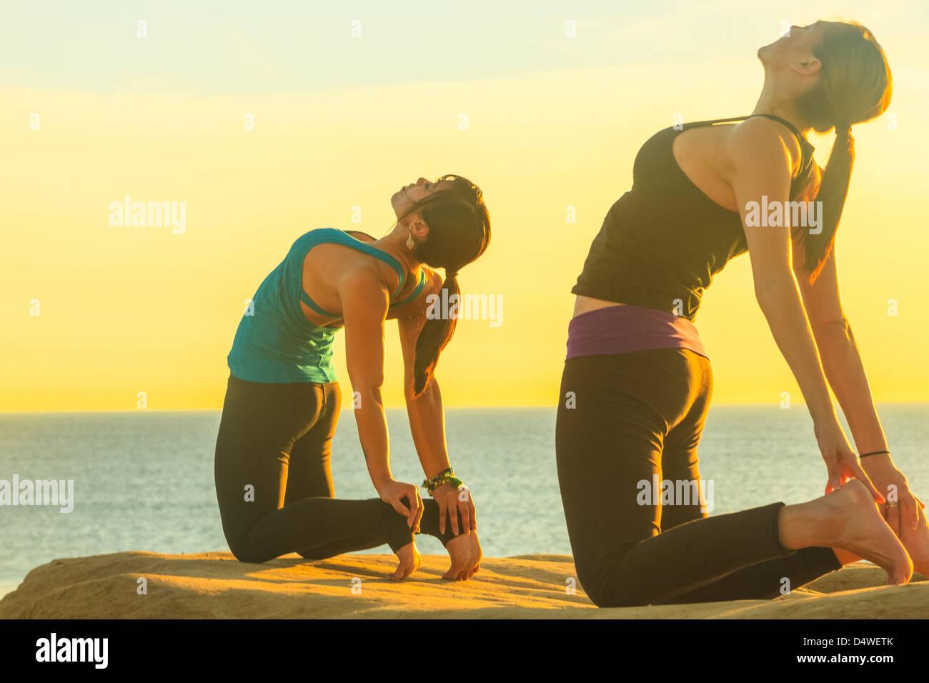Las mujeres que practican yoga sobre formación de roca Foto de stock