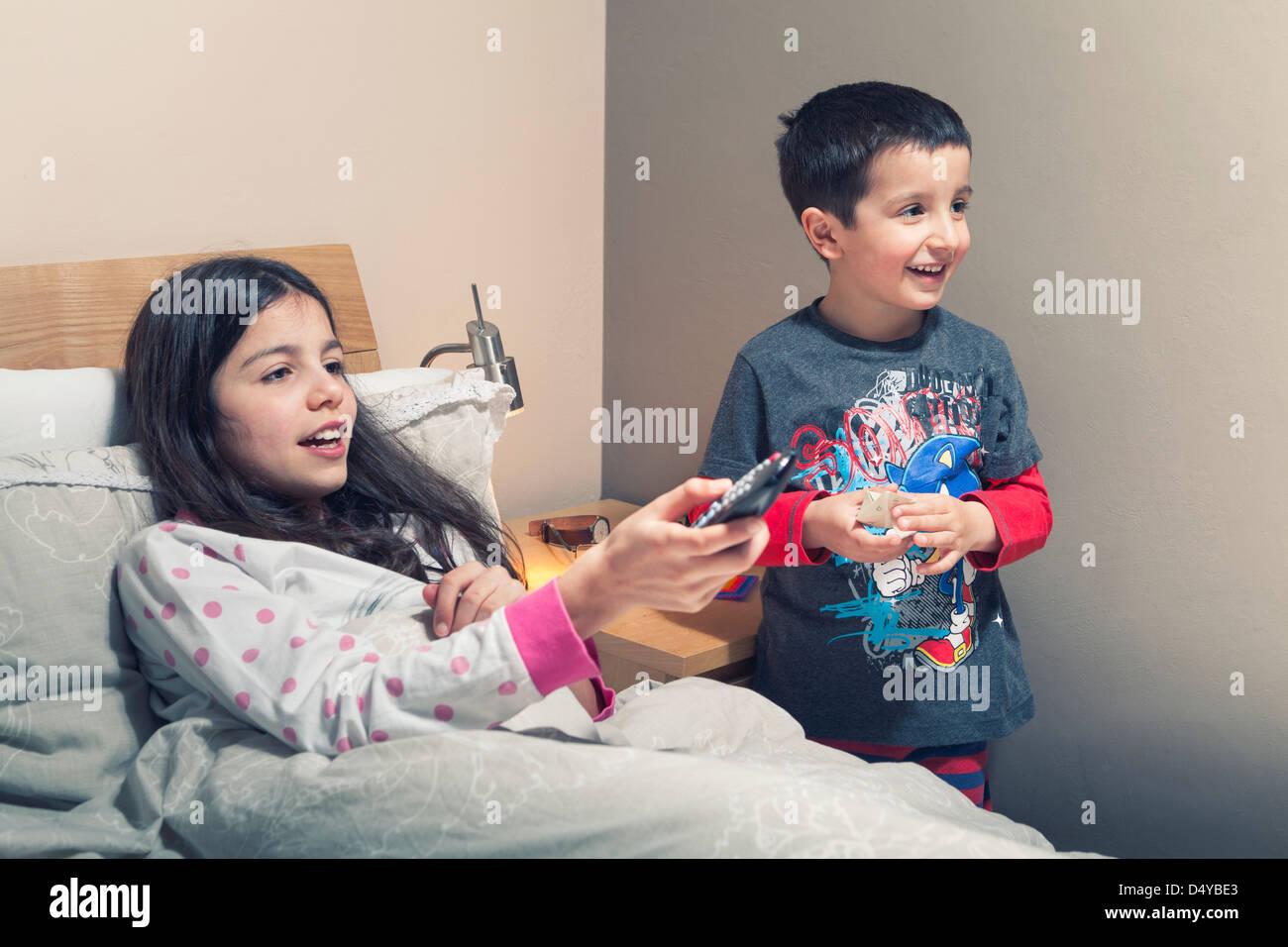 Los niños miran la televisión en la cama Imagen De Stock