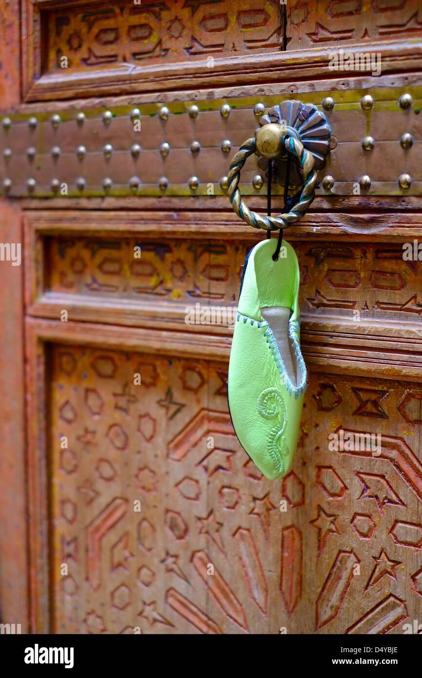 Un marroquí babouche zapata de juguete colgando de un riad tradicional puerta pintadas de madera tallada. Imagen De Stock