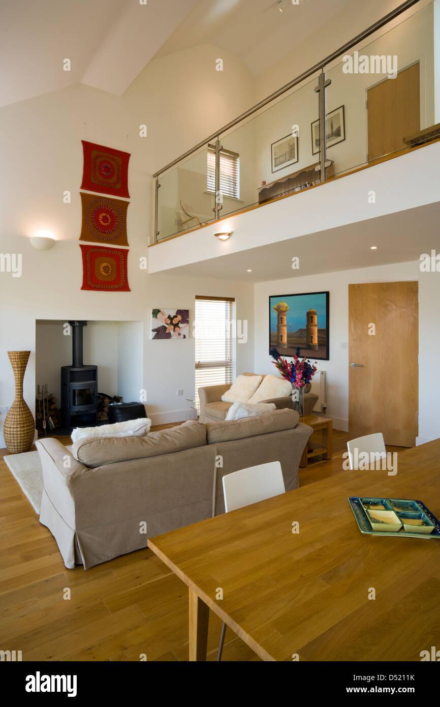 Un plan abierto salón-comedor con techo alto y un pequeño altillo ...