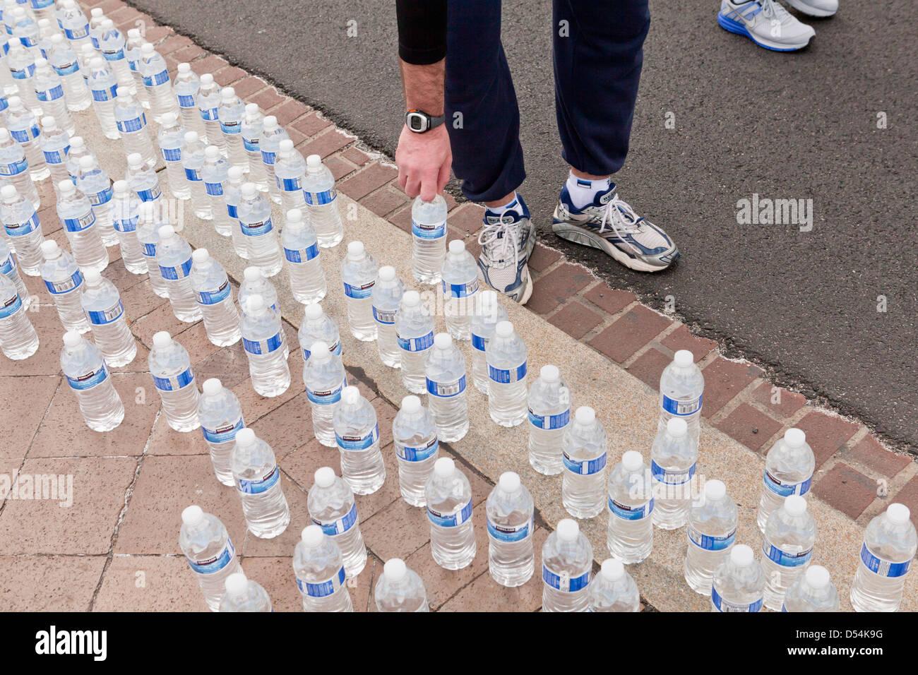 Los corredores de recoger agua embotellada después de la carrera Imagen De Stock