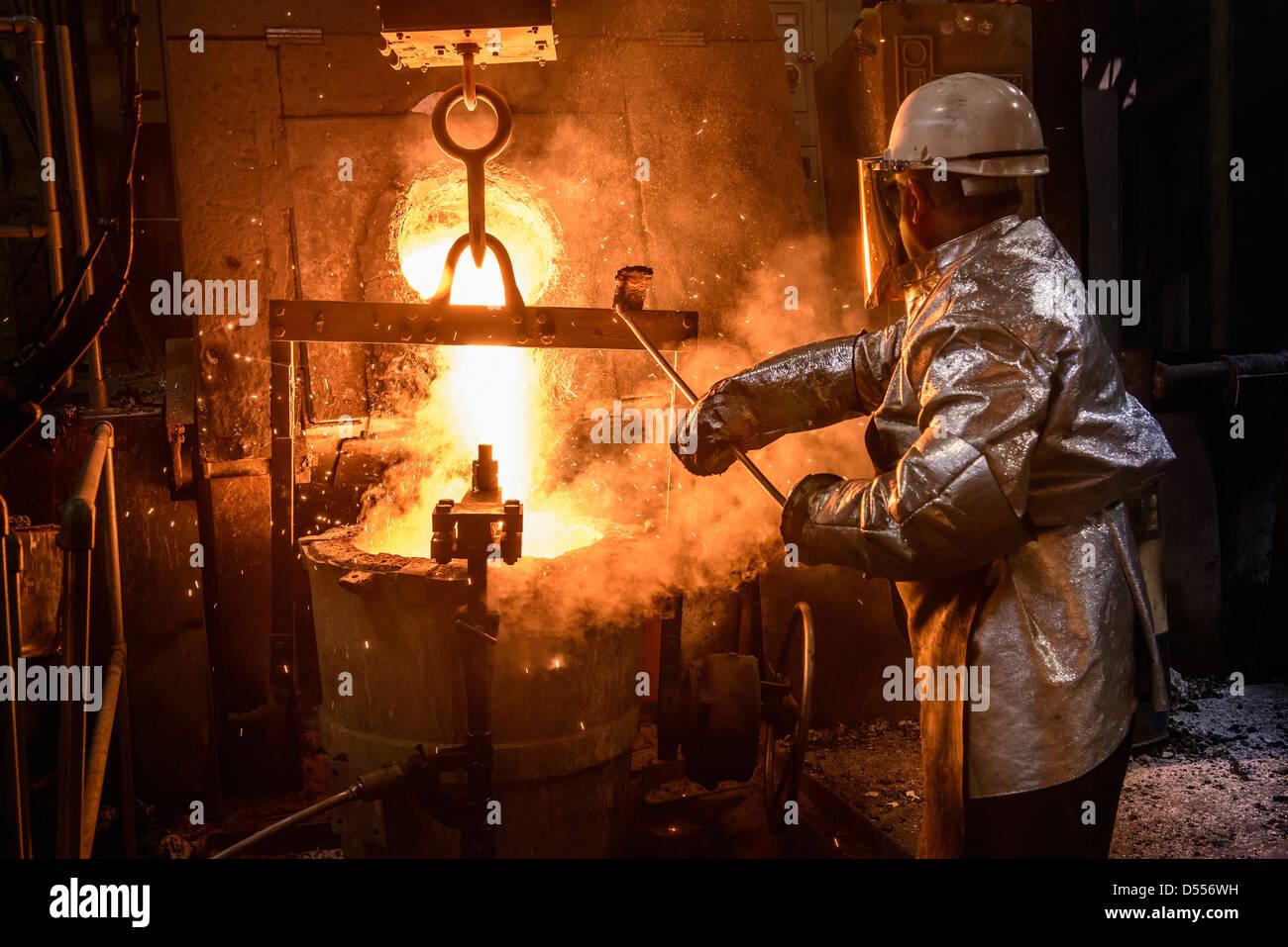 Trabajador vertiendo el metal fundido en la fundición Imagen De Stock
