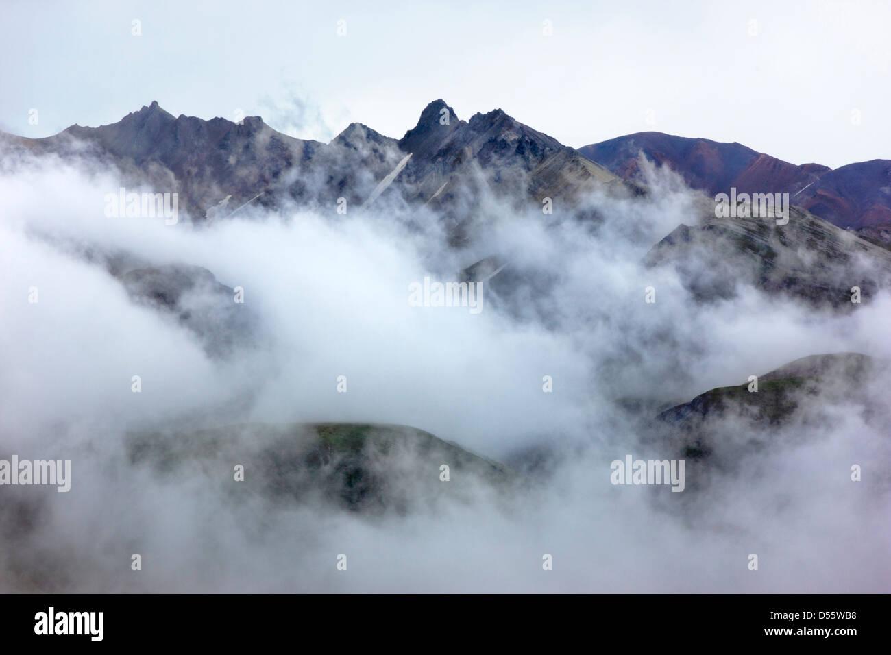 Las nubes bajas, niebla y niebla oscura parcialmente la Cordillera de Alaska, el Parque Nacional Denali, Alaska, EE.UU. Foto de stock