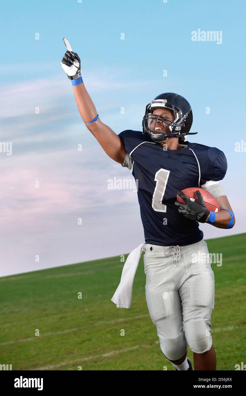 Jugador de fútbol americano africano aclamando en el juego Foto de stock