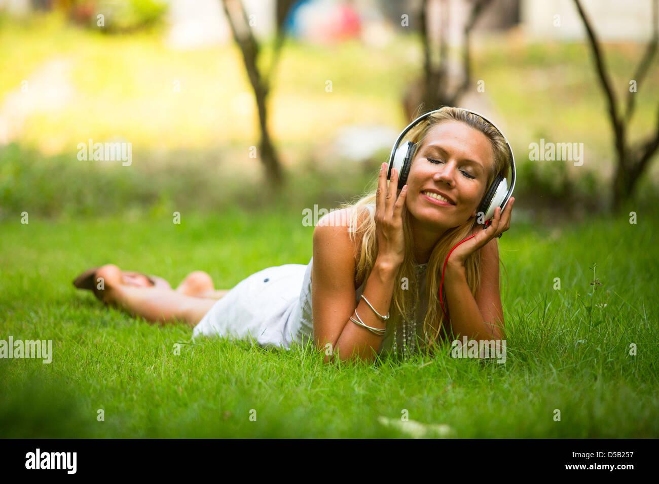 Felicidad emocional chica con auriculares para disfrutar de la naturaleza y música en día soleado. Imagen De Stock