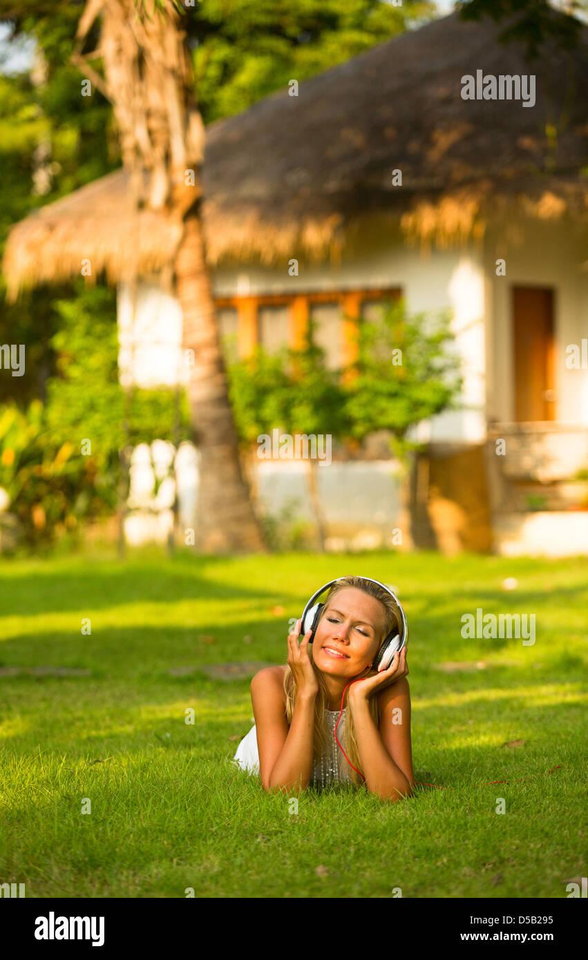 Hermosa chica con auriculares emocional disfrutando de la naturaleza y música en día soleado. Imagen De Stock