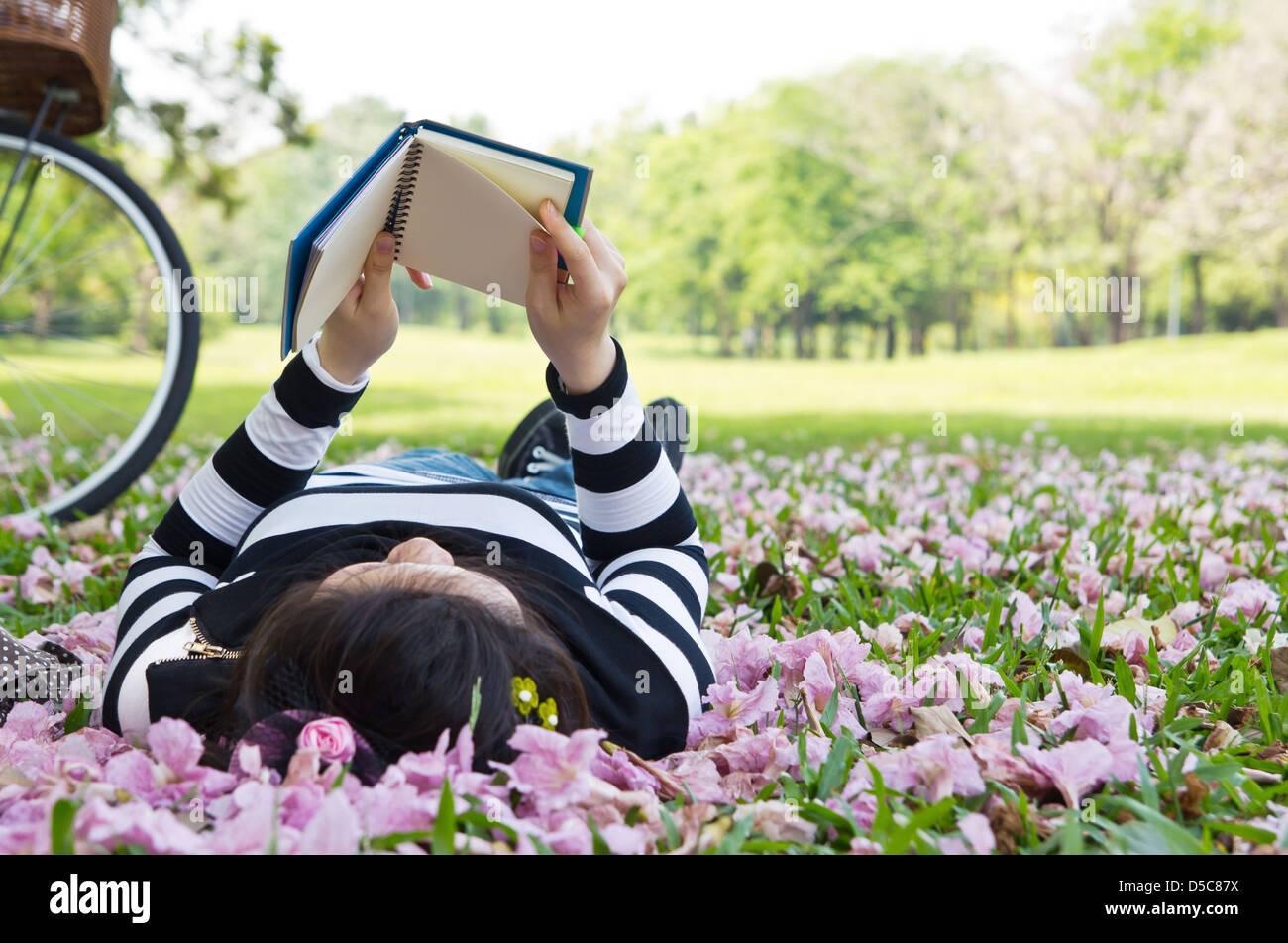 Mujer Asiática leyendo folleto sobre el césped Foto de stock