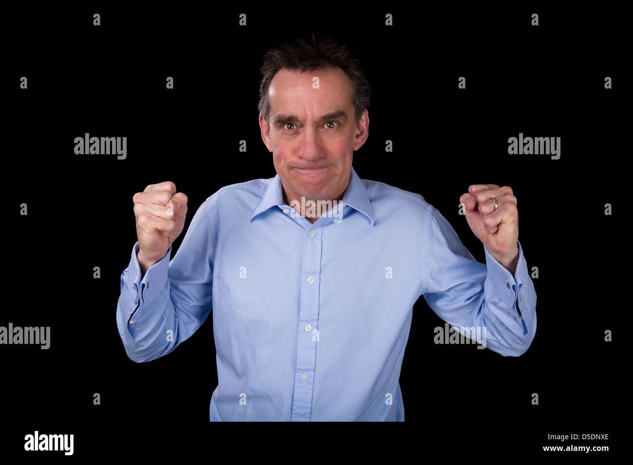 Hombre de negocios de mediana edad enojados agitando puños en frustración fondo negro Imagen De Stock
