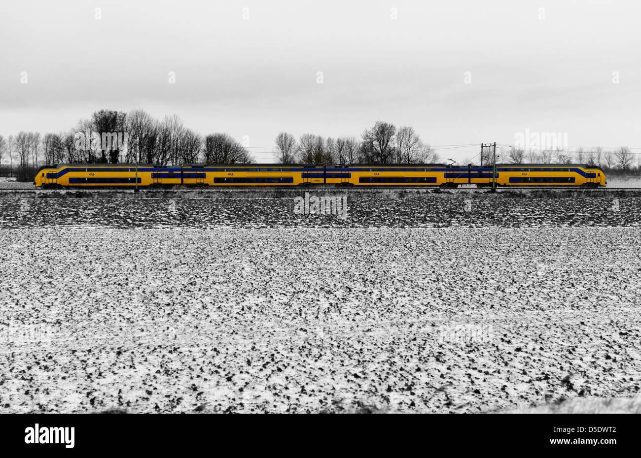 Pasando tren amarillo de los ferrocarriles holandeses en un paisaje cubierto de nieve. Zeeland, Holanda. B/W Imagen De Stock