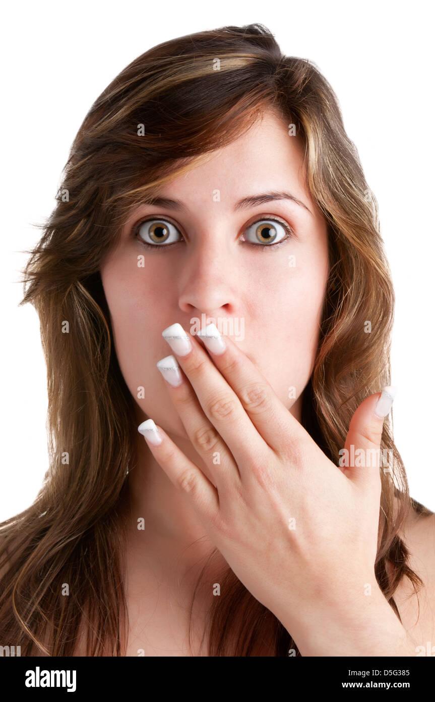Conmocionó a la mujer que cubre su boca con su mano, aislado en un fondo blanco. Imagen De Stock