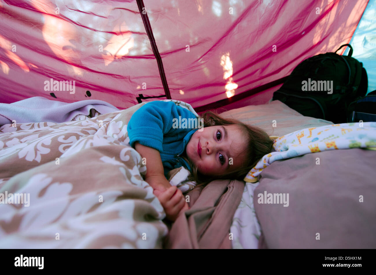 Niña dentro de una carpa de camping acostado contentos en saco de dormir. Imagen De Stock