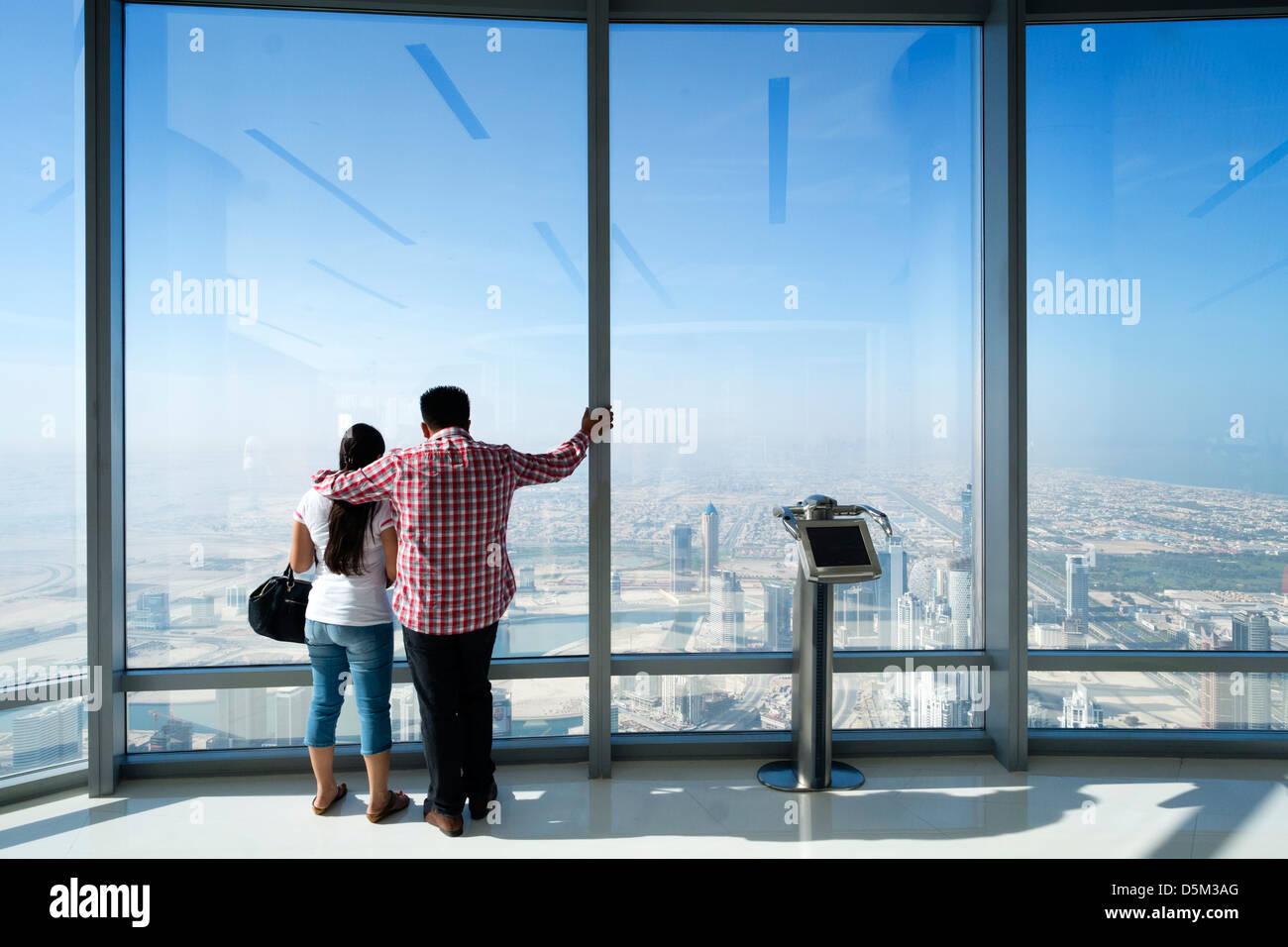 Los turistas mirando a lo largo de Dubai en la parte superior de la plataforma de observación en el Burj Khalifa Foto de stock