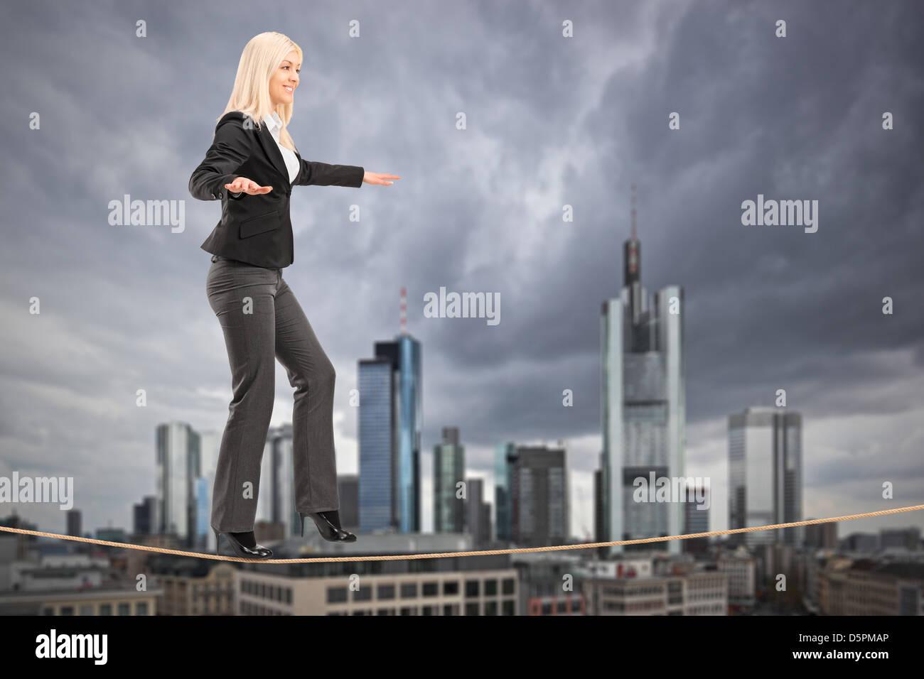 Joven Empresaria caminando sobre una cuerda, con el centro financiero de Frankfurt, Alemania, en el fondo Foto de stock