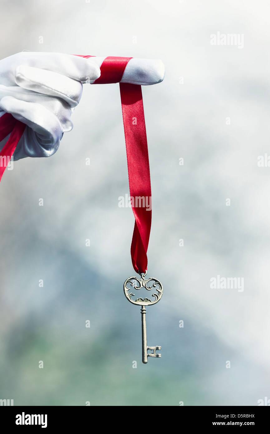 Una mano con guantes blancos sujetando una llave antigua sobre una cinta roja Imagen De Stock