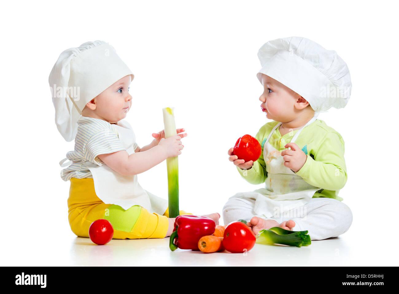 Los bebés chico y chica vistiendo un sombrero de chef con alimentos  saludables verduras Imagen De dd049da3fcf6