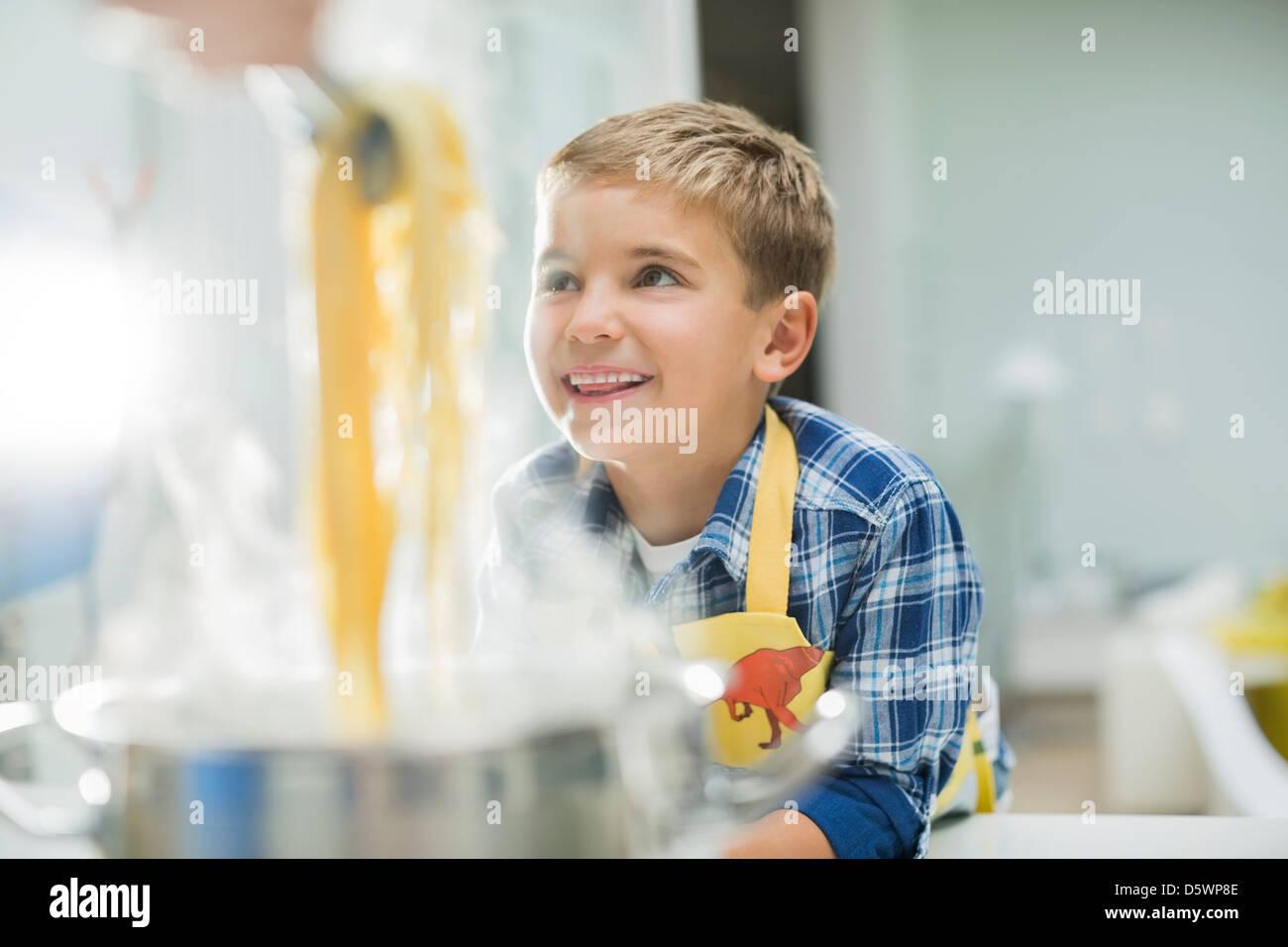 Niño sonriendo en la cocina Foto de stock