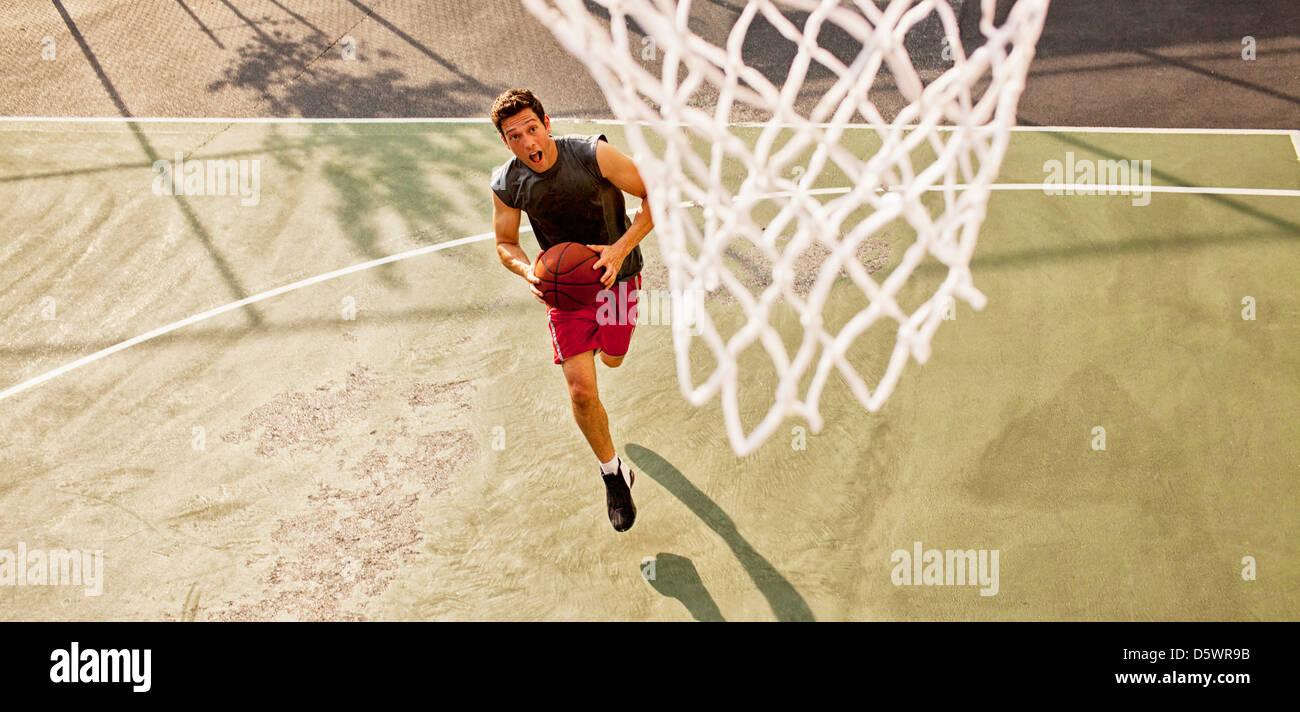 Hombre jugando baloncesto en la cancha Imagen De Stock