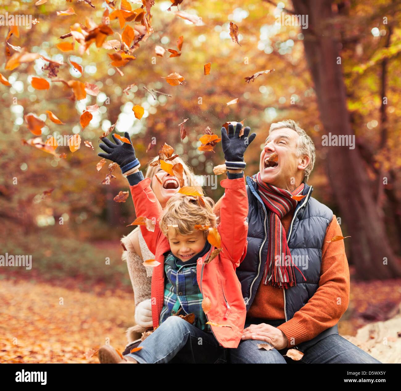 Pareja de ancianos jugando con su nieto en hojas de otoño Foto de stock